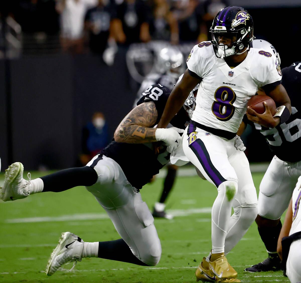 Raiders defensive end Maxx Crosby (98) tries to stop Baltimore Ravens quarterback Lamar Jackson ...