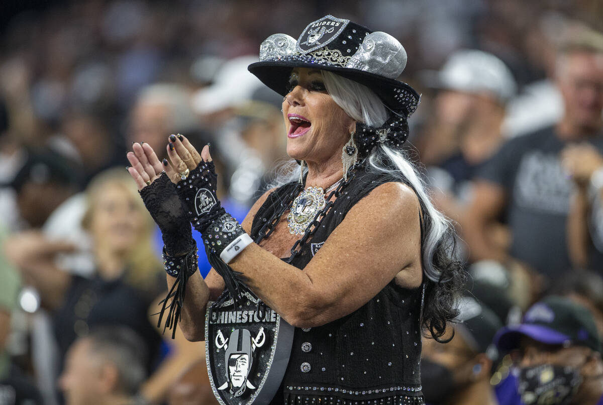 A Raiders fan cheers during the first quarter of an NFL football game against the Baltimore Rav ...