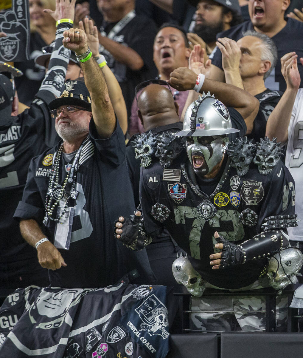 A Raiders fans cheer during the first quarter of an NFL football game against the Baltimore Rav ...