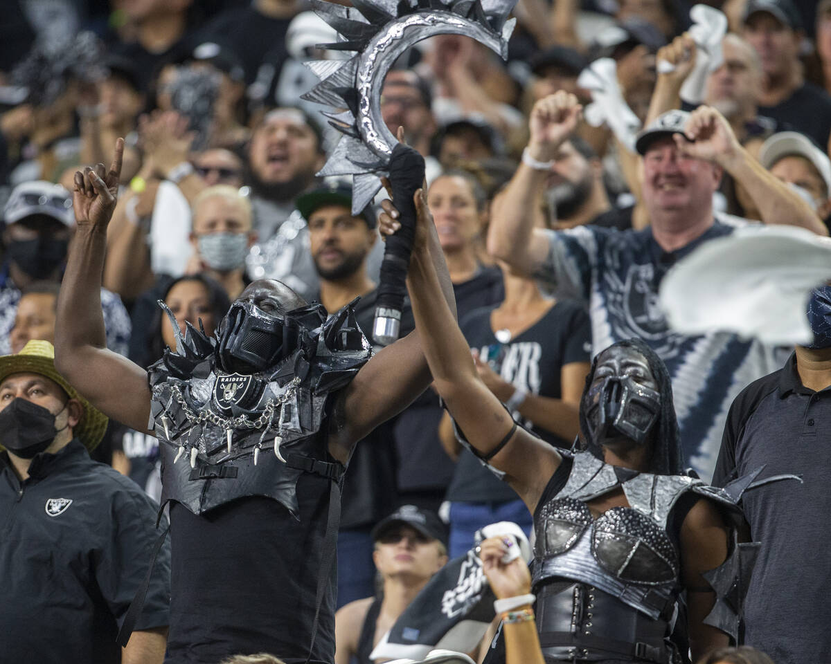 A pair of costumed Raiders fans rally the crowd during the second quarter of an NFL football ga ...