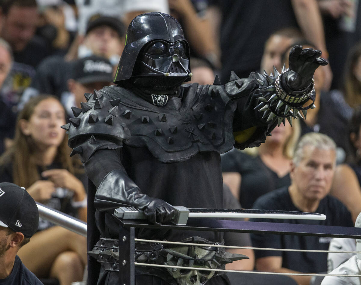 A Raiders fan dressed as Darth Vader looks on during the first quarter of an NFL football game ...