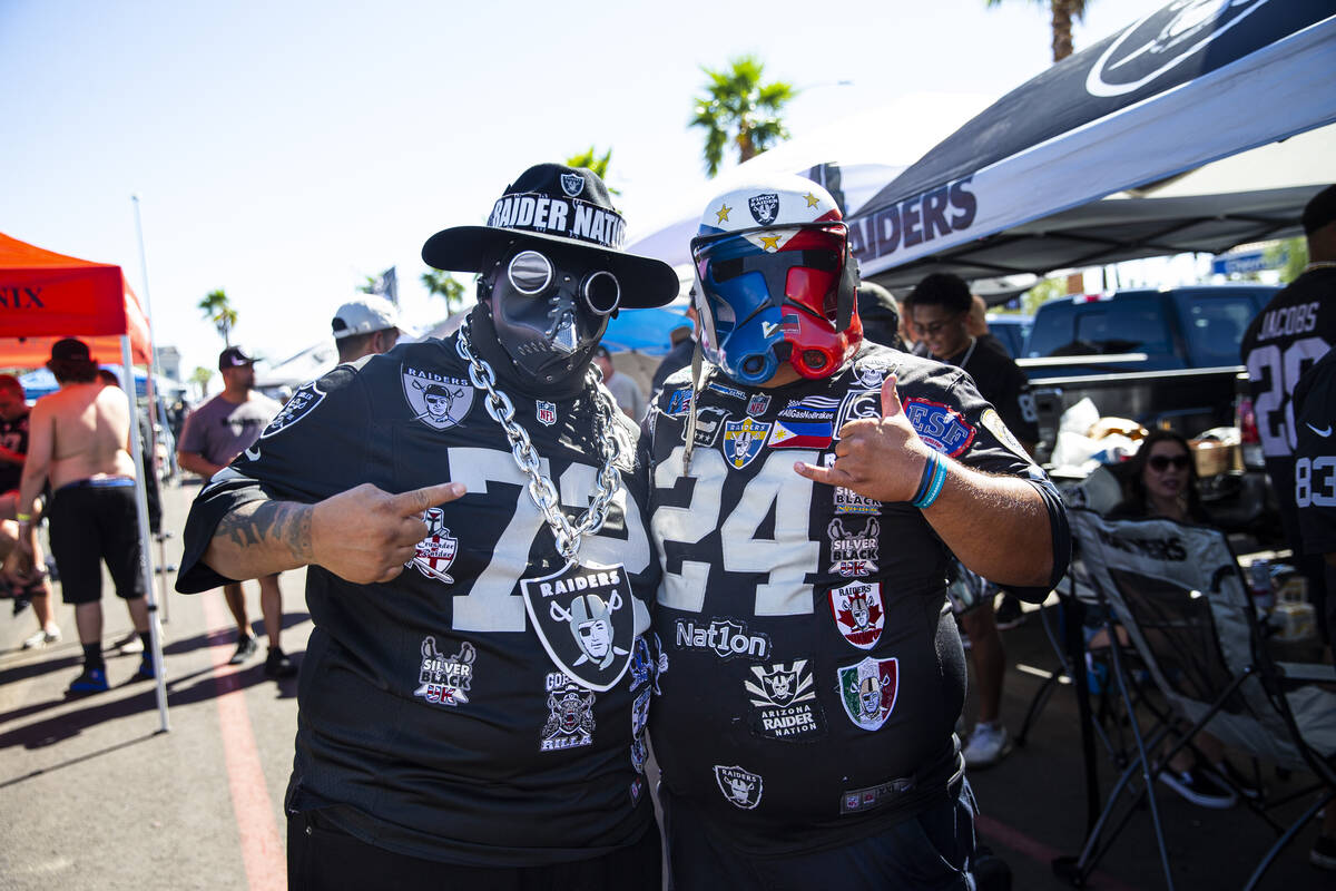 Raiders fans Phillip Prieto, left, and Gene Biyok pose for a portrait during a tailgate before ...