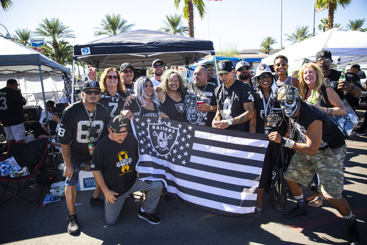 Football fans pose for picture while tailgating before an NFL game between the Raiders and the ...