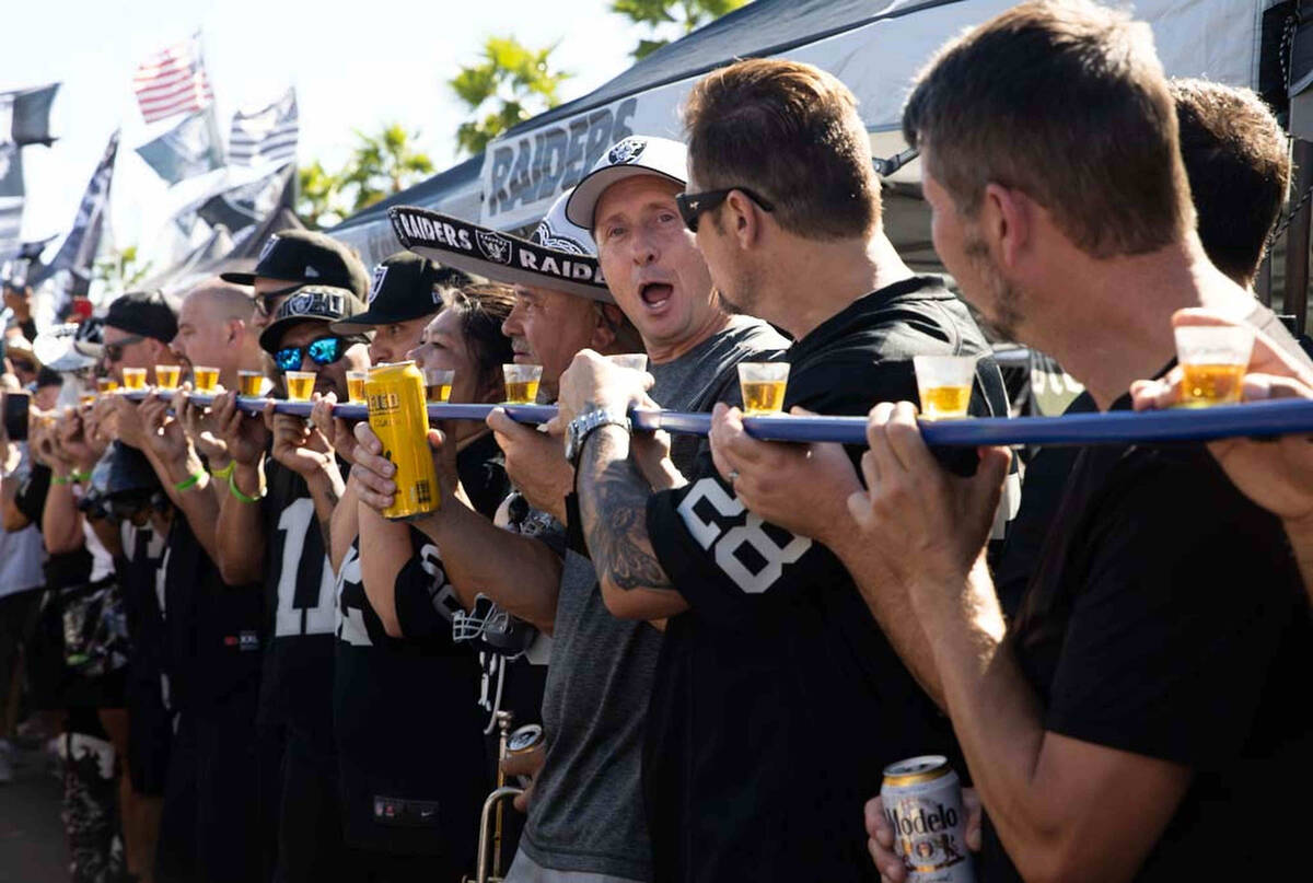Tailgaters lineup for a drink before an NFL football game between the Raiders and Baltimore Rav ...