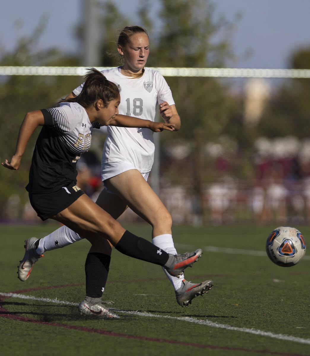 Faith Lutheran's Mia Coe (13) shoots on goal with Arbor View's Alexis Romeo (18) ...