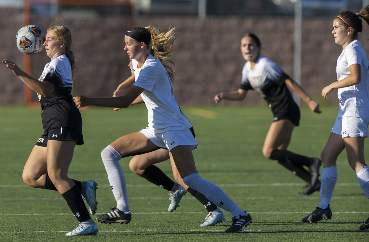 Faith Lutheran's Taylor Folk (26) and Arbor View's Madison Little (14) attempt to ...