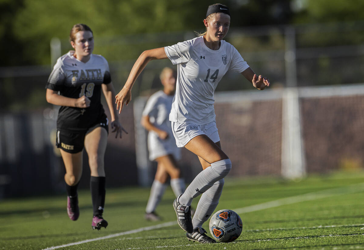 Arbor View's Madison Little (14) pushes the ball up field past Faith Lutheran's C ...
