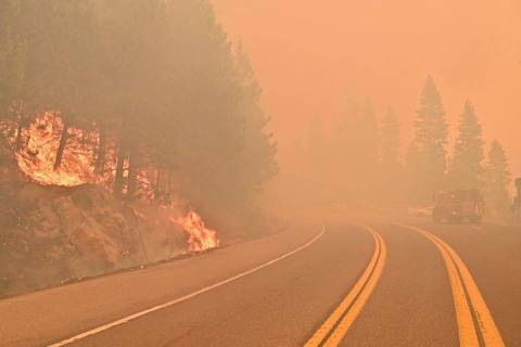 The Caldor Fire burns on both sides of Highway 50 about 10 miles east of Kyburz, Calif., on Thu ...