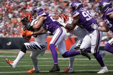 Cincinnati Bengals running back Joe Mixon, left, is tackled by Minnesota Vikings free safety Ha ...
