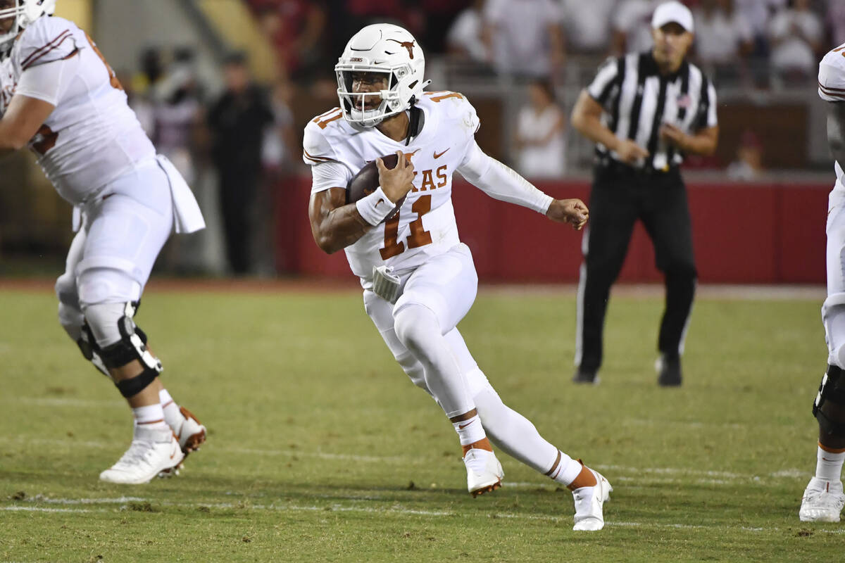 Texas quarterback Casey Thompson (11) runs the ball against Arkansas during an NCAA college foo ...