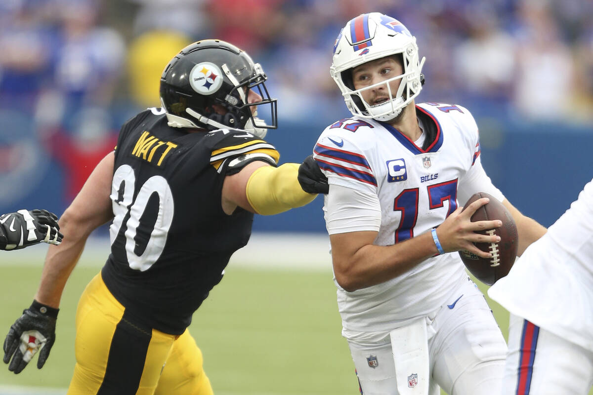 Buffalo Bills quarterback Josh Allen (17) runs past Pittsburgh Steelers linebacker T.J. Watt (9 ...