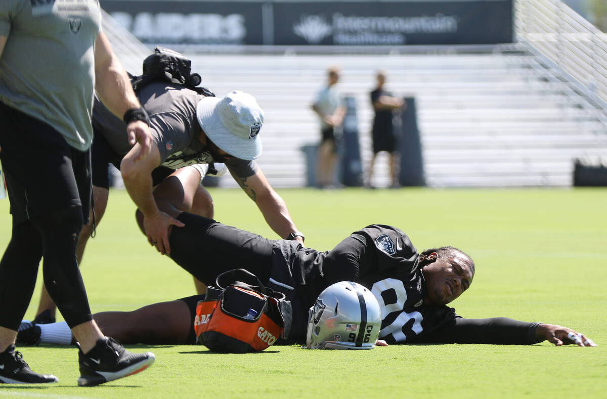 A trainer works on Raiders defensive tackle Darius Philon (96) who suffered an injury during te ...