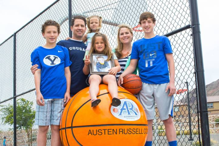 Kyler, Troy, Maddie, Payton, Deedra and Collin Russell with photo of Austen Russell, 9, stand n ...