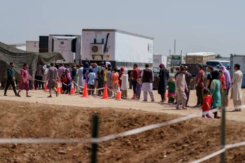 Afghan refugees line up for food outside a dining hall at Fort Bliss' Doña Ana Village whe ...
