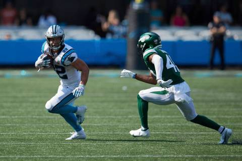 Carolina Panthers running back Christian McCaffrey (22) tries to avoid the tackle attempt of Ne ...