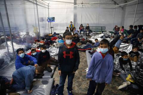 Young children stand or sleep insides a pod at the U.S. Customs and Border Protection holding f ...