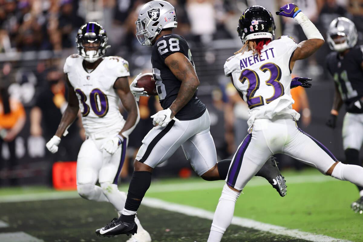 Raiders running back Josh Jacobs (28) runs for a touchdown under pressure from Baltimore Ravens ...