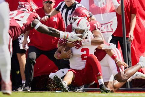 Nebraska quarterback Adrian Martinez (2) is brought down by Oklahoma linebackers Nik Bonitto (1 ...