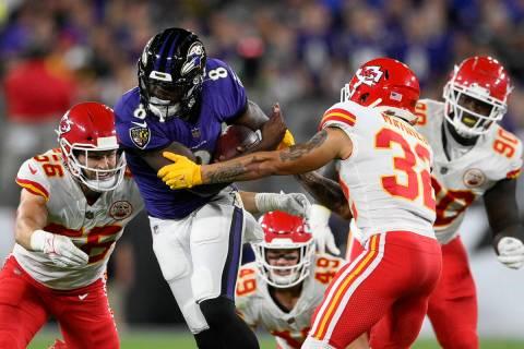 Baltimore Ravens quarterback Lamar Jackson (8) rushes against Kansas City Chiefs defenders in t ...