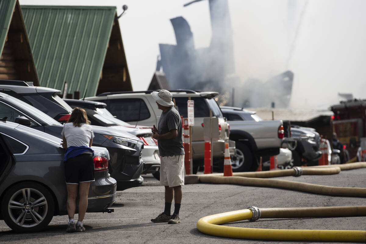 Residents, including Anthony Armas, right, watch as firefighters battle a blaze at Mount Charle ...