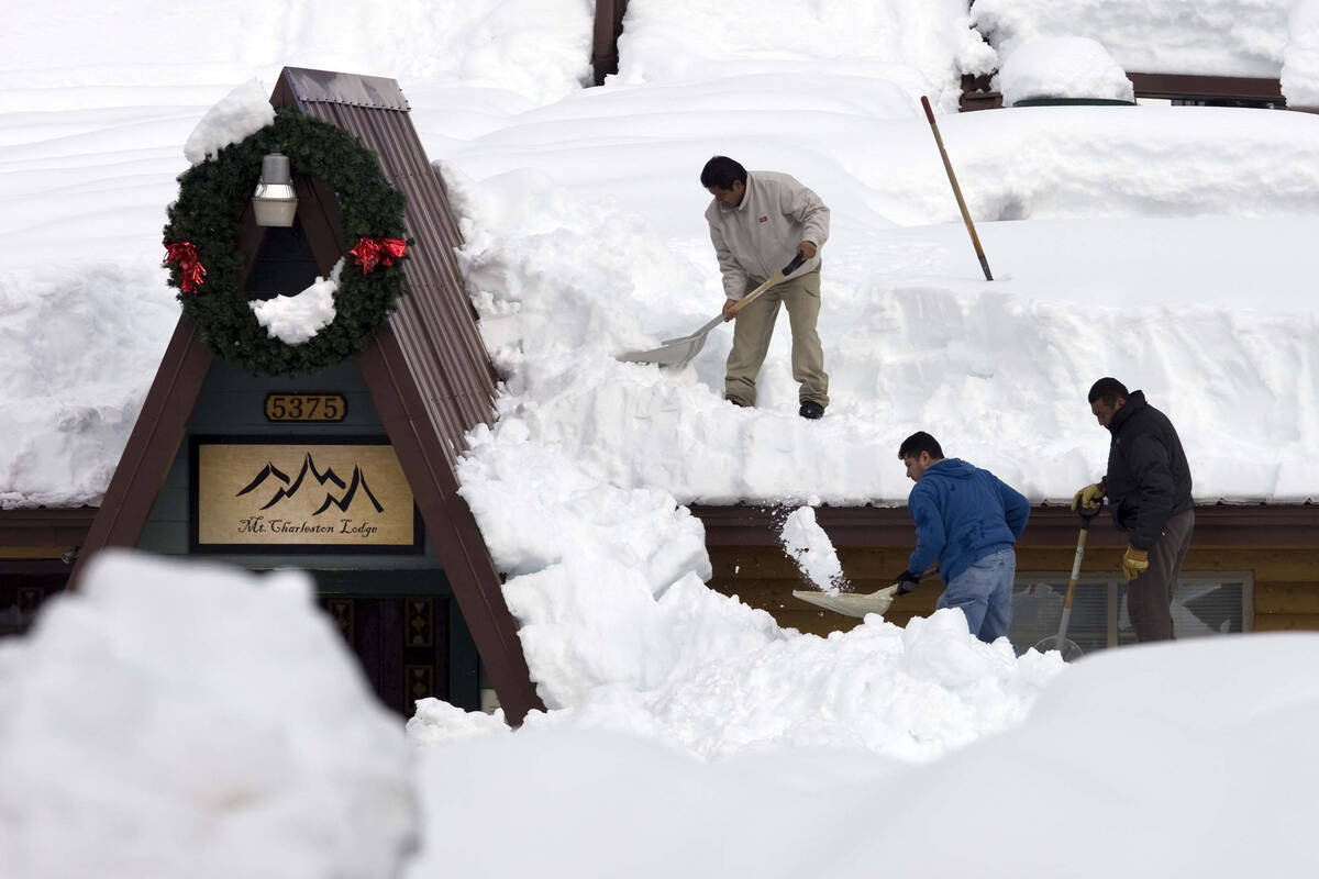Workers, from left, Sergio Reyes, Manuel Franco, and Jose Trujillo shovel snow off the roof of ...