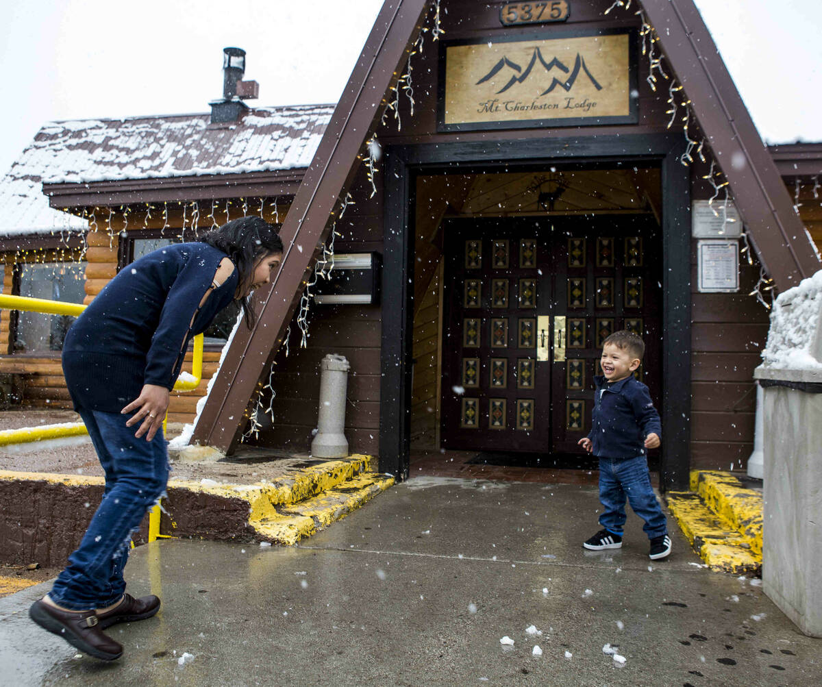 Nofi Simanungkalit and her son, David, 2, enjoy snow outside of the Mount Charleston Lodge on T ...