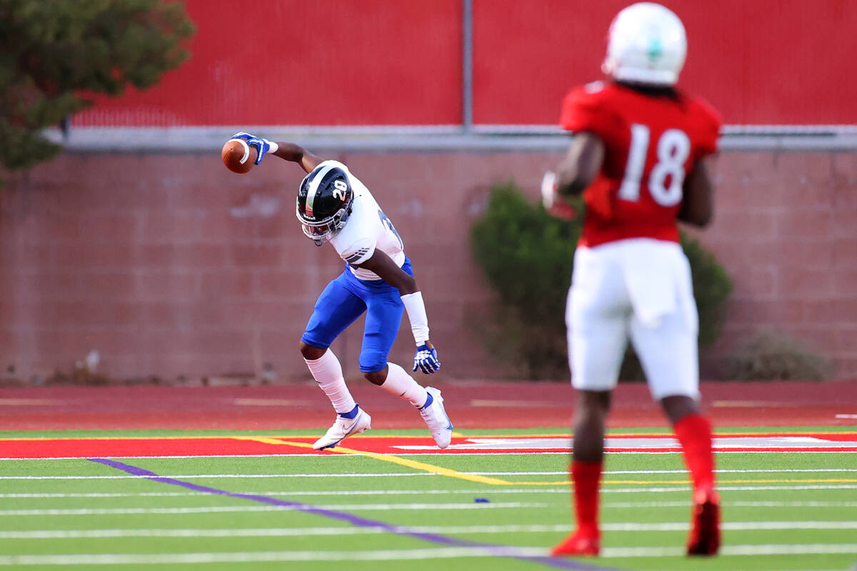 Desert Pines Isaiah Rubin (20) celebrates a touchdown after intercepting the ball in the first ...