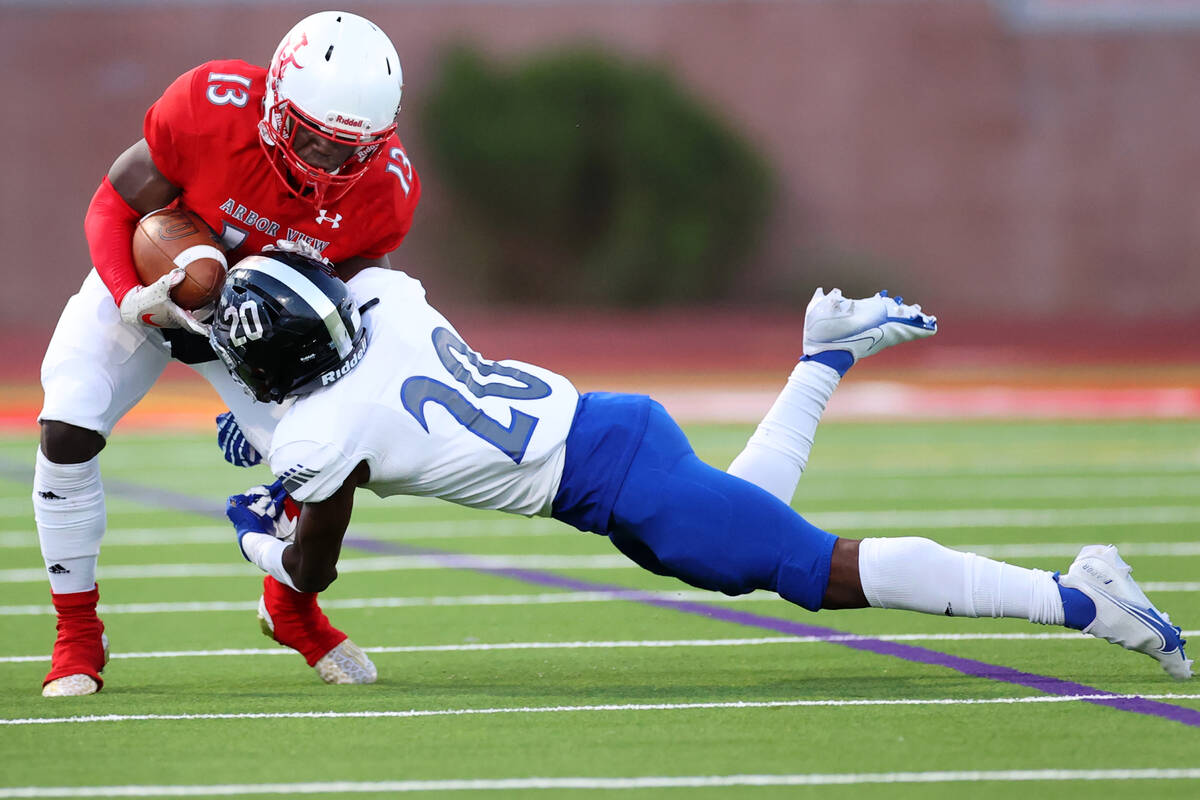 Arbor View's D'Andre Washington (13) is tackled by Desert Pines Isaiah Rubin (20) in the first ...