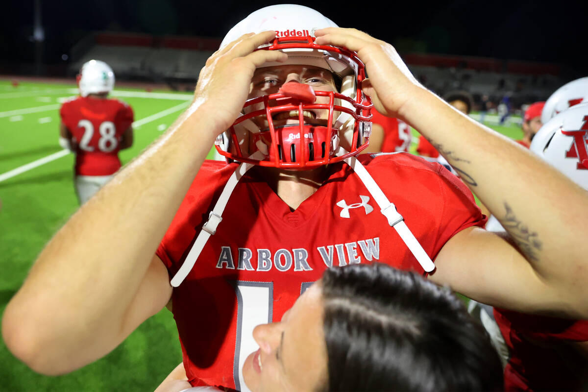 Arbor View's quarterback Kyle Holmes (17) receives a hug from his mother Jessica Holmes after d ...