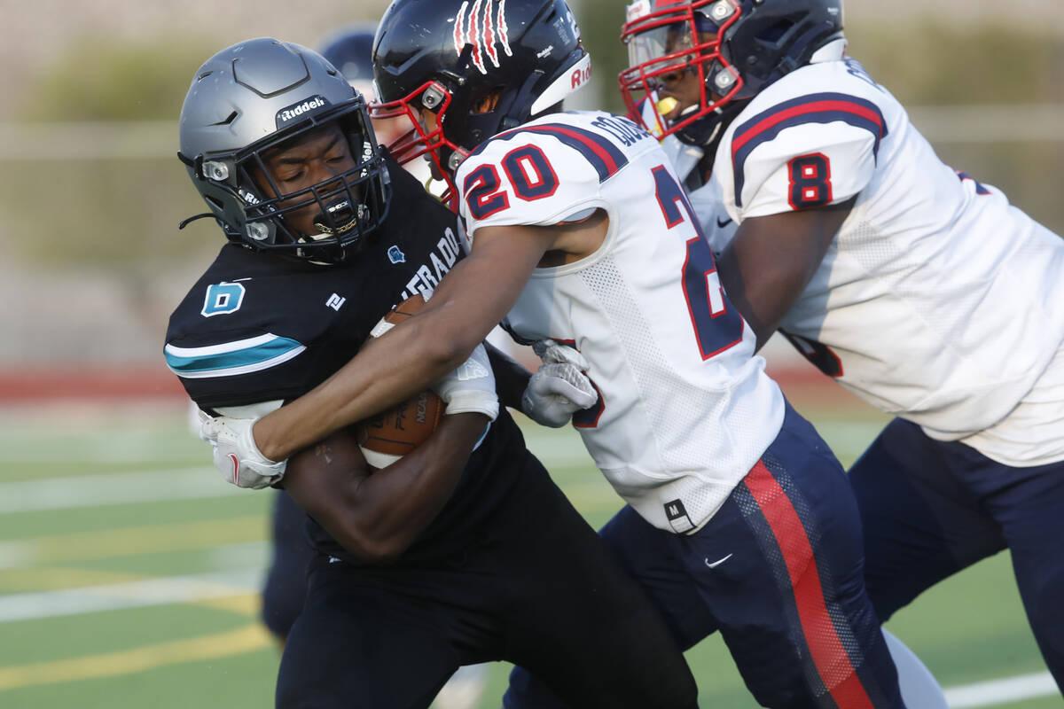 Silverado High School's John Agounke (6) is tackled by Coronado High School's Preston McQueen ( ...