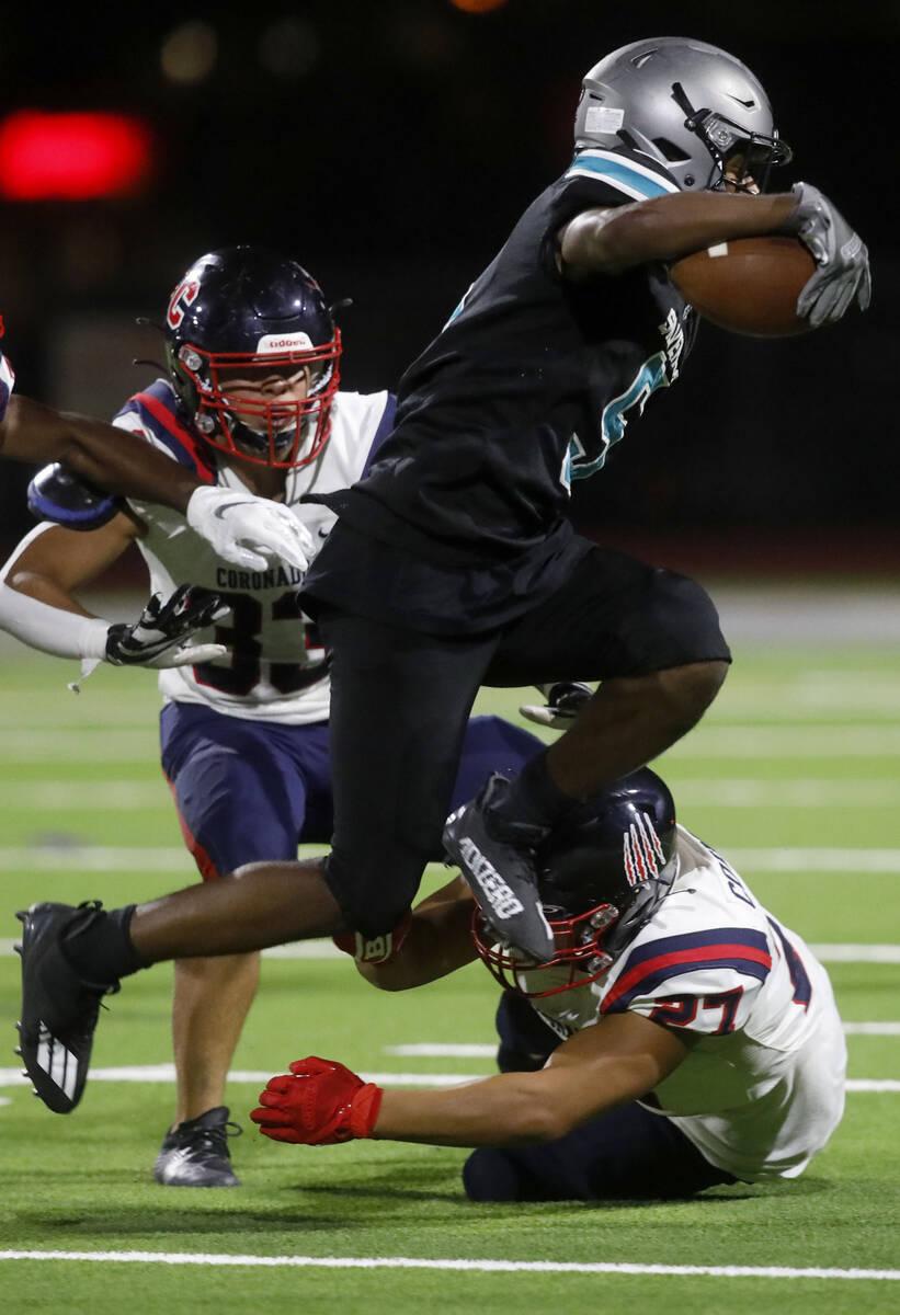 Silverado High School's Jaden Thrower (5) jumps over Coronado High School's Mohammad Maali (27) ...