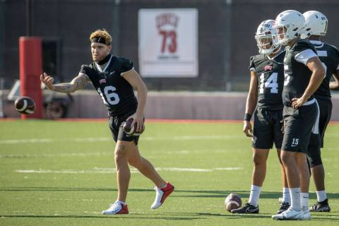 UNLV quarterback Tate Martell (16, left) tosses in a ball to a teammate as other quarterbacks l ...