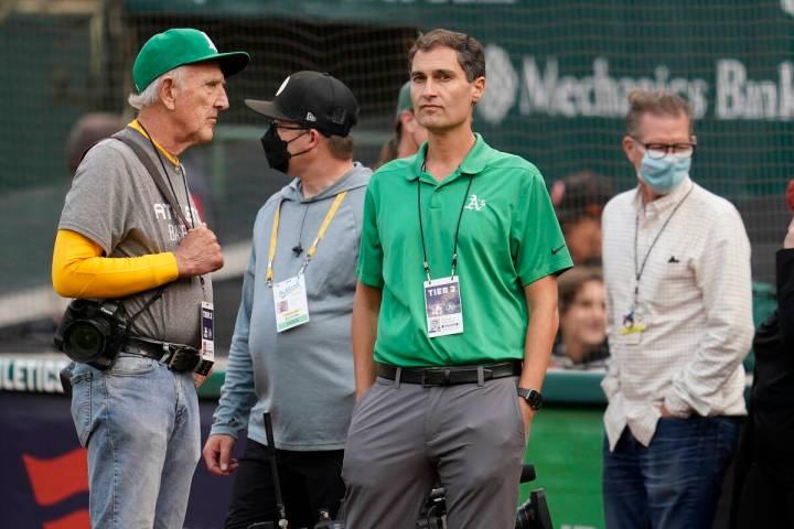 Oakland Athletics President Dave Kaval, center, talks with photographer Michael Zagaris, left, ...