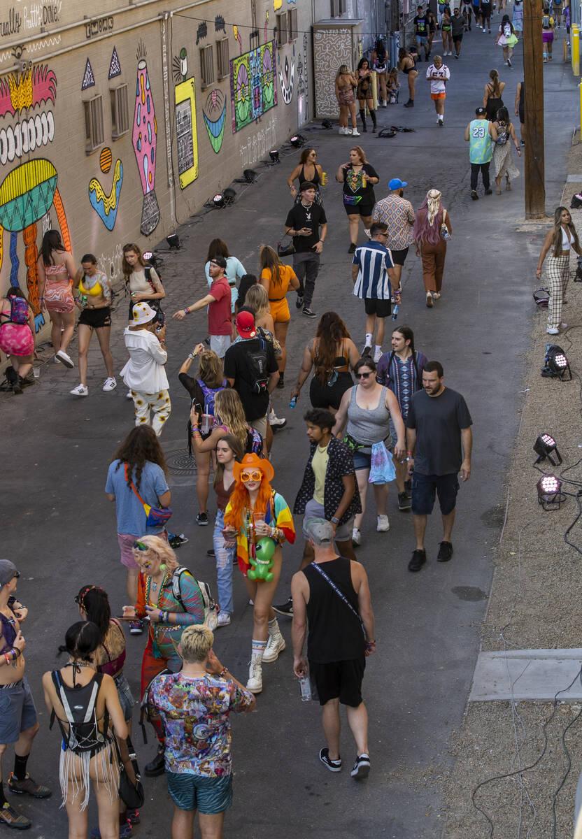 Orang-orang berjalan di sepanjang gang di Fremont Street yang dilukis dengan seni baru pada hari pertama Life is ...