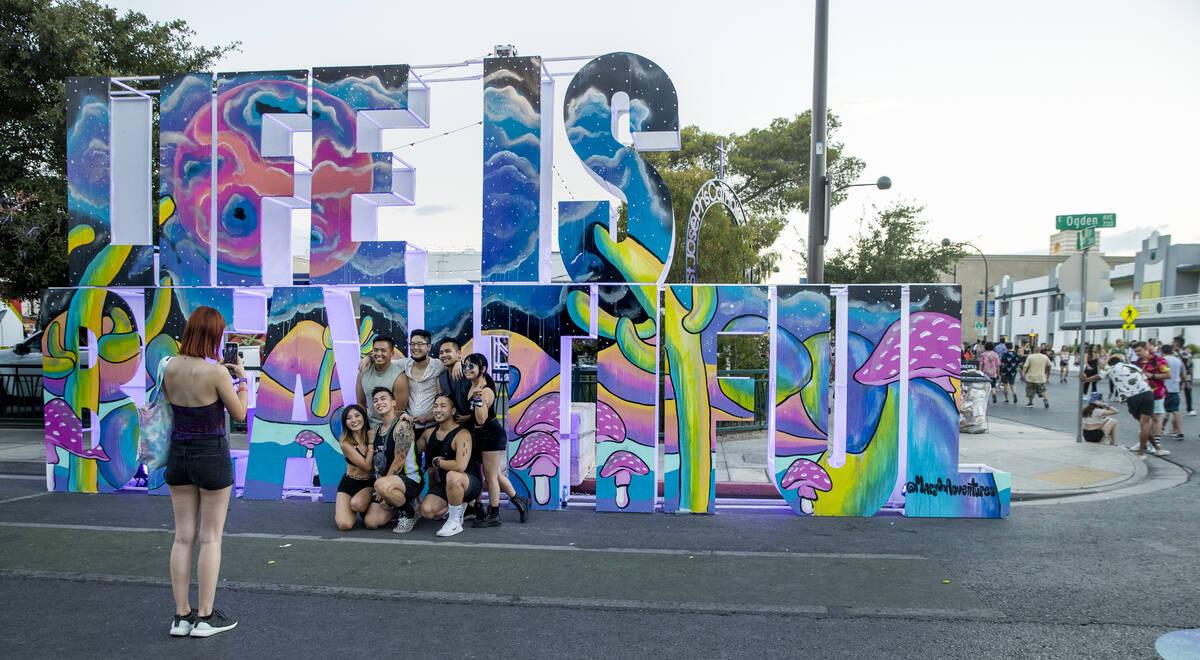 Teman-teman berkumpul tentang patung di sepanjang East Ogden Avenue pada hari pertama Life is Beautiful di ...