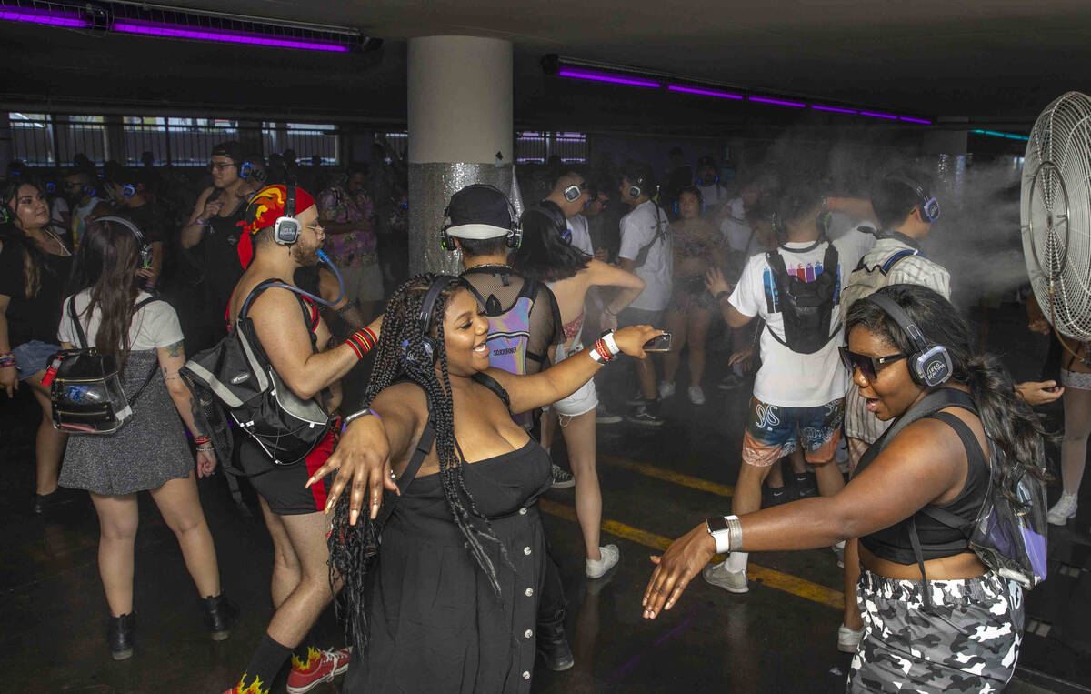 People dance within a silent disco in a parking lot garage off of South 7th Street during day o ...
