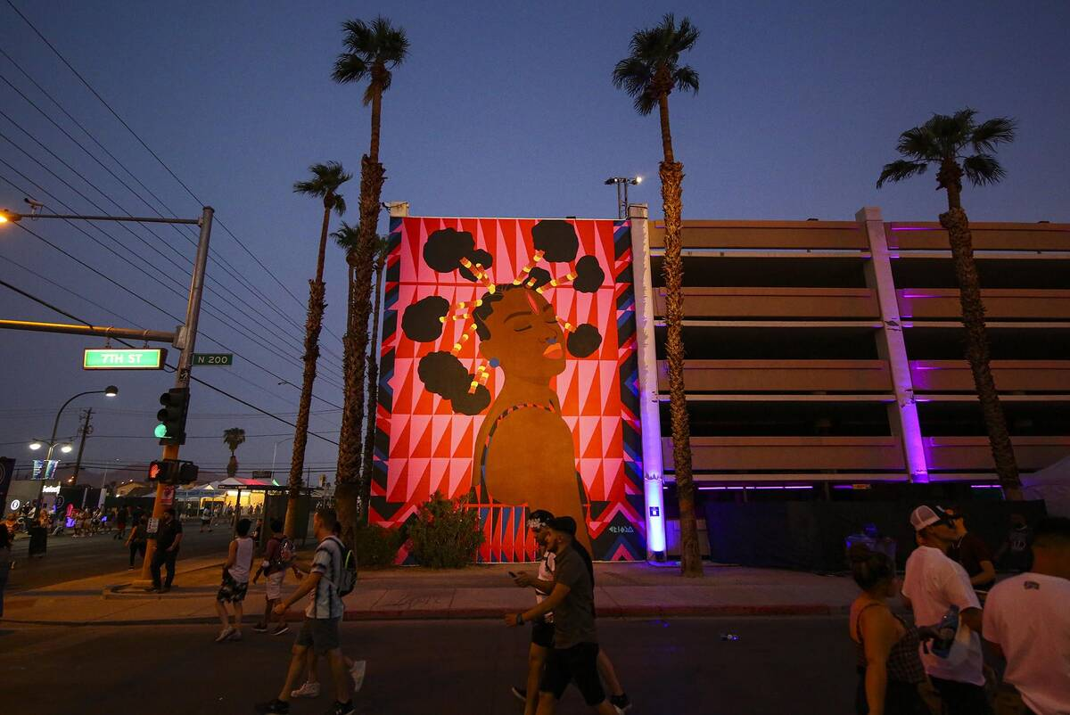 Attendees walk  by a mural during the last  time  of the Life is Beautiful festival successful  downtown La ...