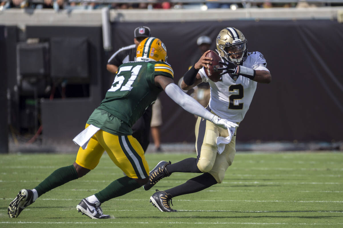New Orleans Saints quarterback Jameis Winston (2) rolls out to pass while being defended by Gre ...