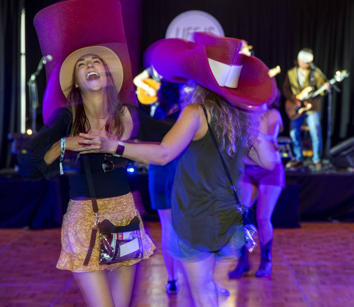 Beth Sassani, left, and Kellie Brunty dance with their big cowboy hats on as The Rhyolite Sound ...