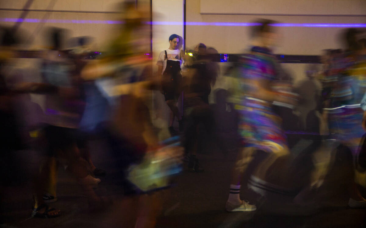 Attendees stream along a neon-lit alleyway during day one of Life is Beautiful on Friday, Sept. ...