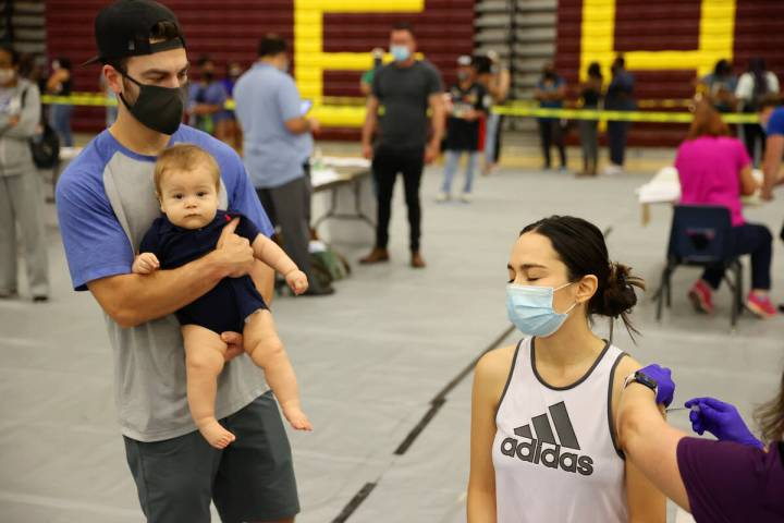 Ursula Moreno of Las Vegas receives the COVID-19 vaccine as her husband Keenan Laffoon and 11-m ...