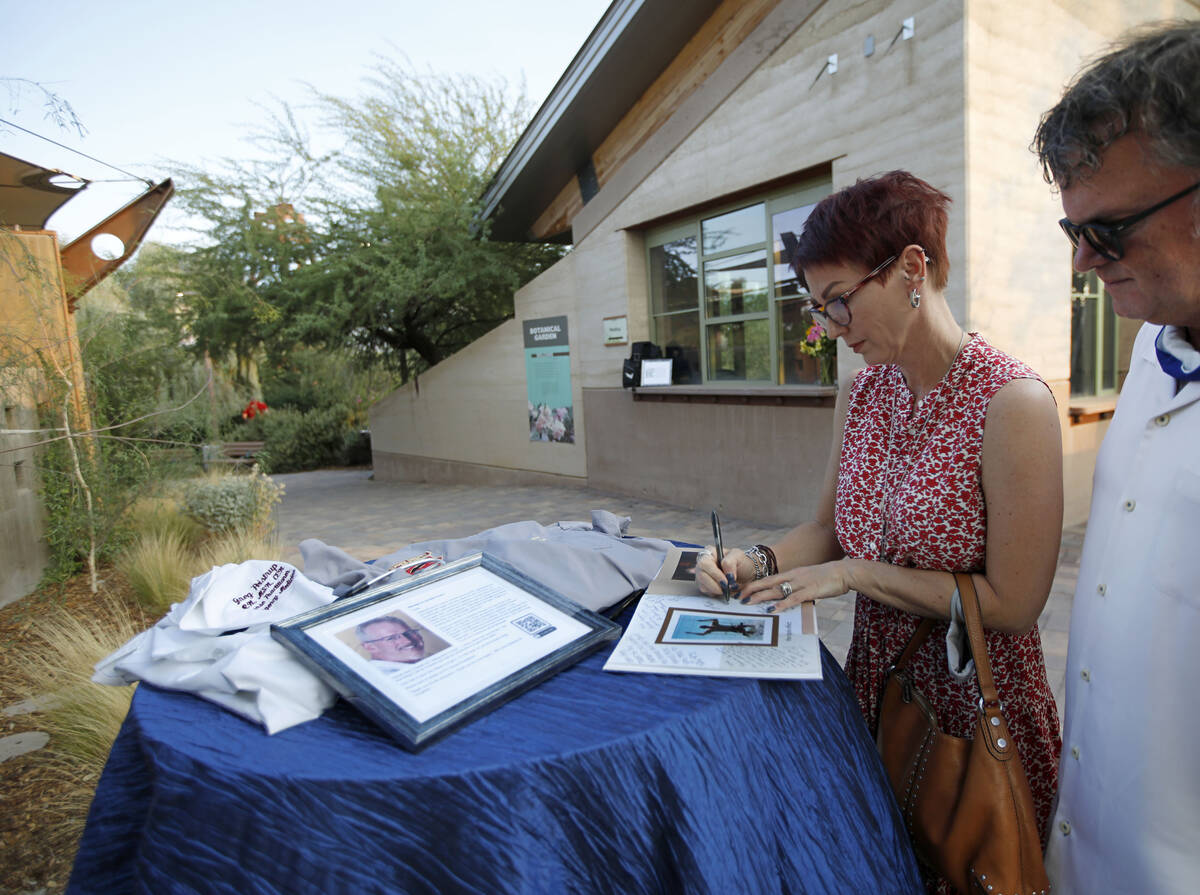 Kelly Slaughter of Las Vegas writes a message on a book when she and her husband Kevin arrive a ...
