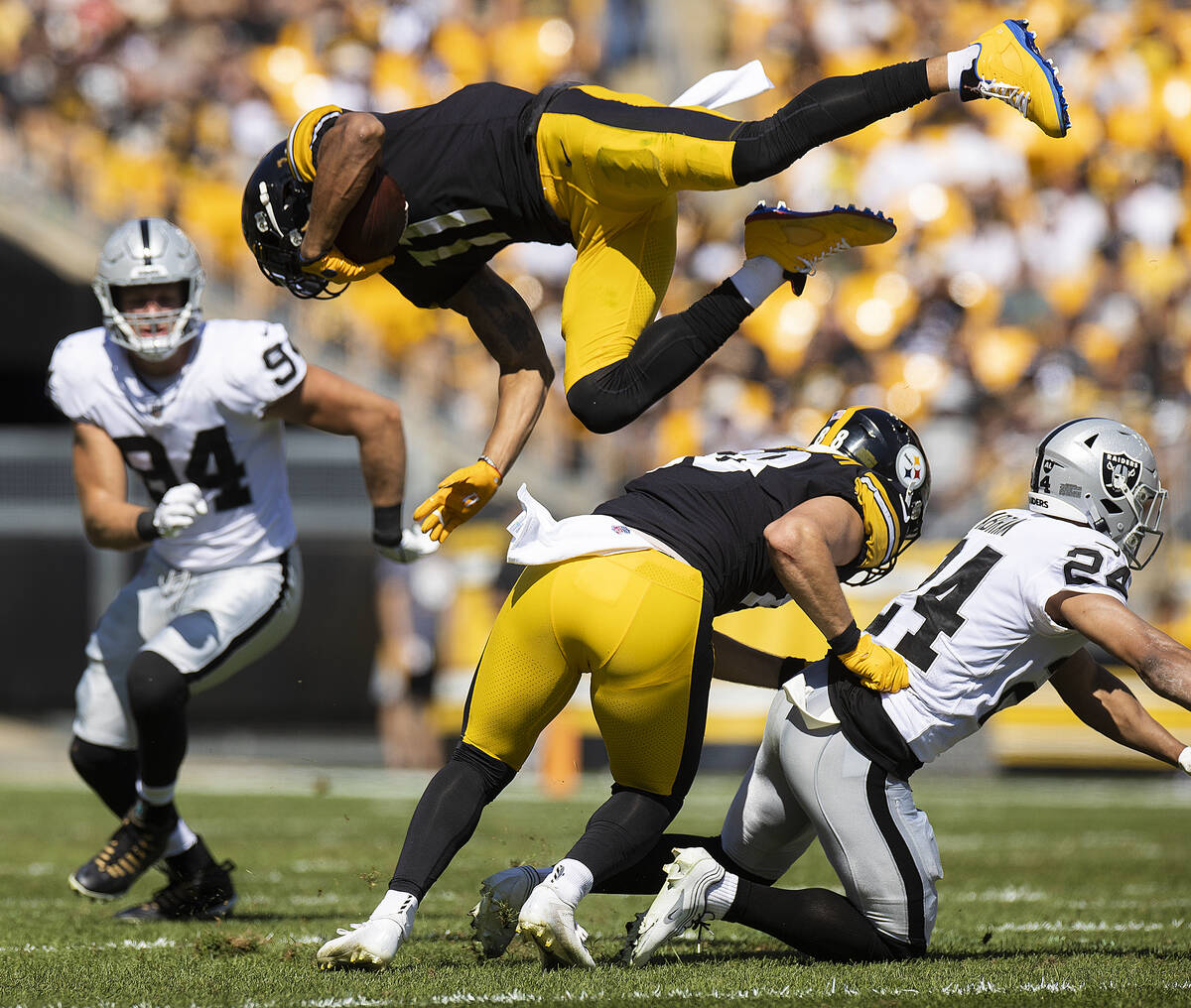 Pittsburgh Steelers wide receiver Chase Claypool (11) is up ended by Raiders defensive back Joh ...