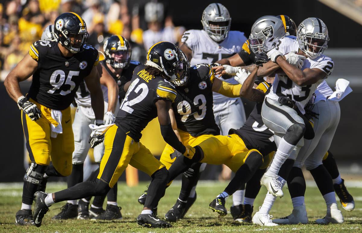Raiders running back Kenyan Drake (23) breaks through a hole past Pittsburgh Steelers middle li ...