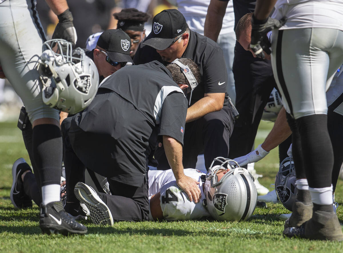 Raiders quarterback Derek Carr (4) remains down after getting hit as he threw a touchdown pass ...