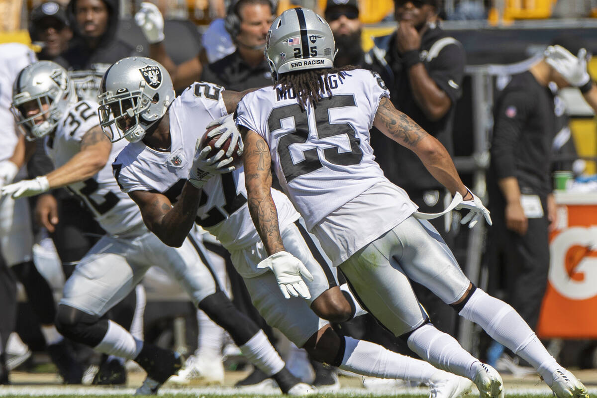 Raiders cornerback Trayvon Mullen (27) runs back an interception with teammates Raiders safety ...