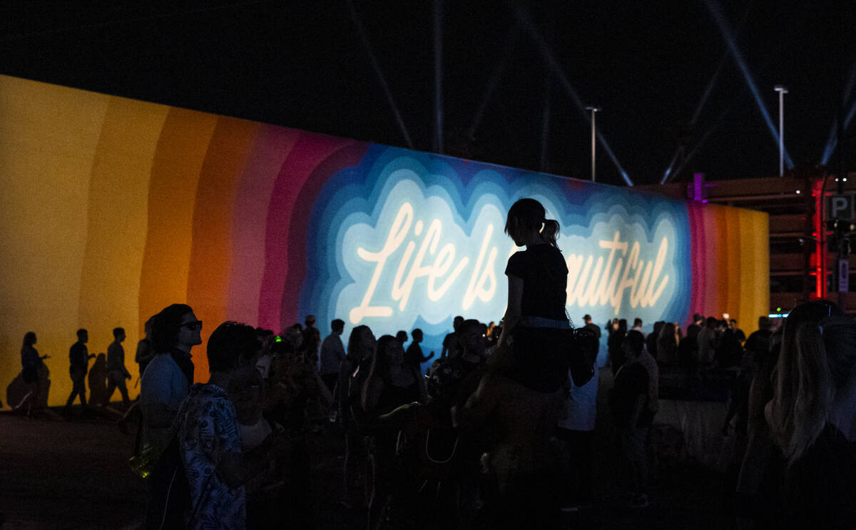 Attendees are silhouetted against a mural during the final day of the Life is Beautiful festiva ...
