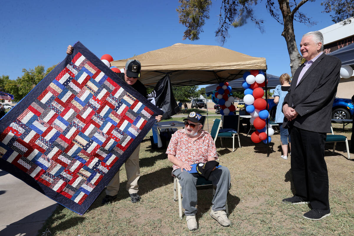 World War II veteran Vincent Shank, center, is gifted a quilt from Patrick Nary, left, as Gov. ...
