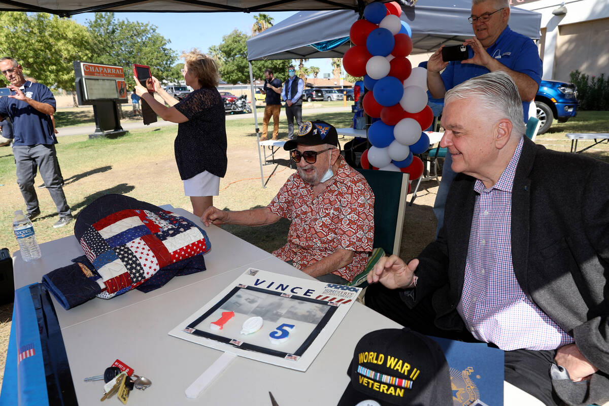 World War II veteran Vincent Shank, left, watches a parade in his honor with Gov. Steve Sisolak ...