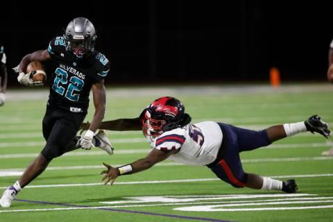 Silverado High School's Caden Harris (22) carries a ball against Coronado High School's Ryan Ha ...